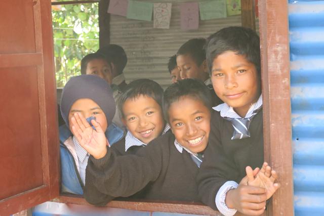 仮設教室の窓から笑顔をみせる子どもたち