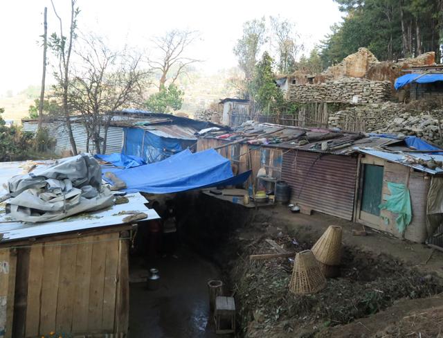 自力でなんとか作った仮設住宅。屋根が飛ばないよう重石をのせます。後方に写っているのは崩れたままの住宅