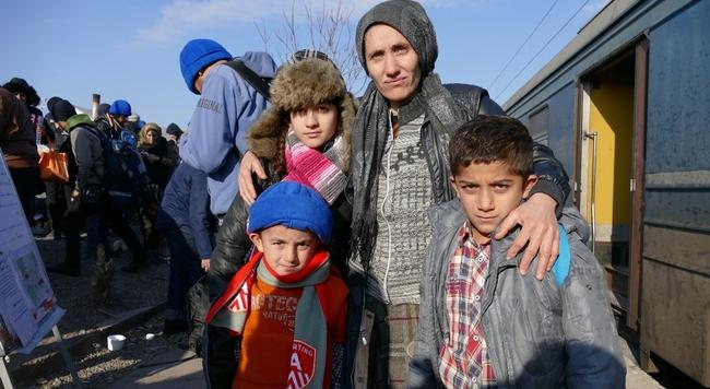 防寒着として配布された帽子をかぶった男の子(左下)と家族